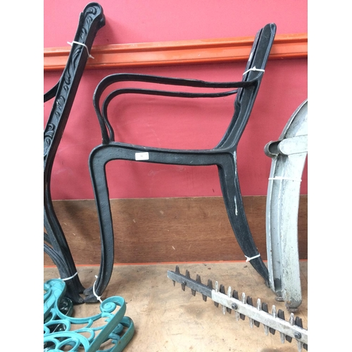 51 - A PAIR OF BLACK PAINTED CAST IRON GARDEN BENCH ENDS...