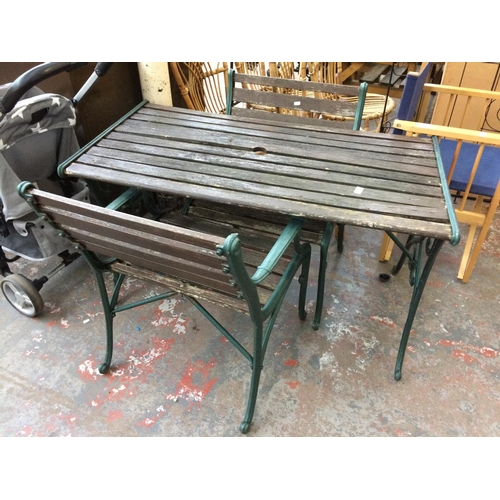 29 - A THREE PIECE CAST IRON ORNATE GARDEN SET COMPRISING RECTANGULAR TABLE AND TWO MATCHING ARM CHAIRS...