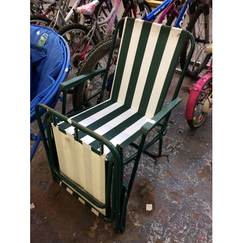 43 - TWO GREEN METAL FOLDING CAMPING CHAIRS WITH STRIPPED UPHOLSTERY...