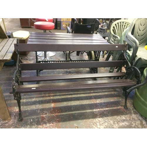 26 - A TWO PIECE WOODEN SLATTED AND CAST IRON ORNATE PATIO SET TO INCLUDE THREE SEAT BENCH AND MATCHING R...
