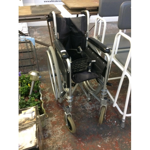 18 - A BLACK AND SILVER ENIGMA FOLDING WHEELCHAIR...