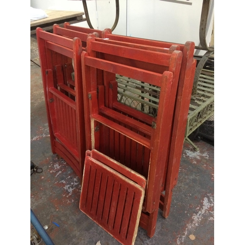 23 - SIX RED PAINTED FOLDING WOODEN CHAIRS...