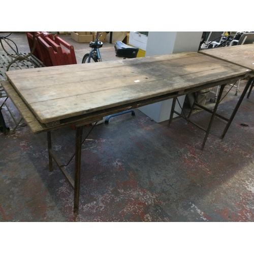 27 - TWO VINTAGE FOLDING TRESTLE TABLES ON METAL SUPPORTS...
