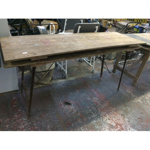 28 - TWO VINTAGE FOLDING TRESTLE TABLES ON METAL SUPPORTS...