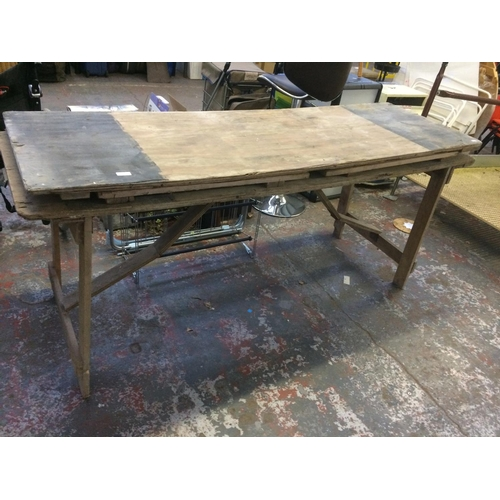 29 - TWO VINTAGE FOLDING TRESTLE TABLES ON WOODEN SUPPORTS...