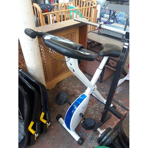 18 - A BLUE AND WHITE DAVINA MCCALL EXERCISE BIKE WITH DIGITAL READOUT (W/O)...