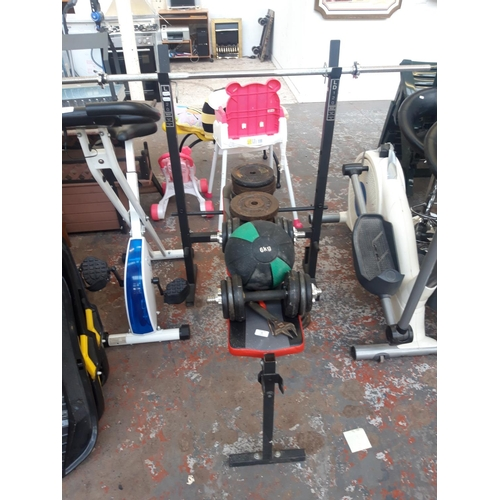 19 - A BLACK METAL EXERCISE BENCH WITH MEDICINE BALL AND METAL YORK AND BODYTORQUE WEIGHTS...