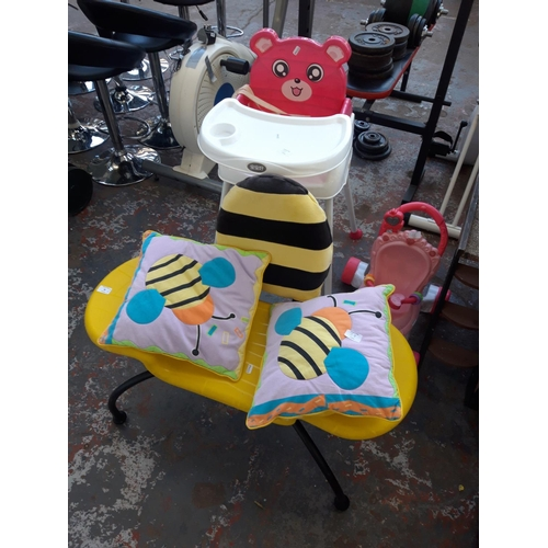 38 - FIVE BABY ITEMS TO INCLUDE A PINK AND WHITE HIGH CHAIR, BLACK AND YELLOW BEE CHAIR, MATCHING CUSHION...