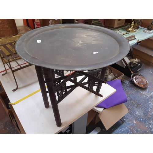 359 - A VINTAGE MIDDLE EASTERN COLLAPSIBLE HARDWOOD TABLE WITH LARGE CIRCULAR BRASS CHARGER TOP...