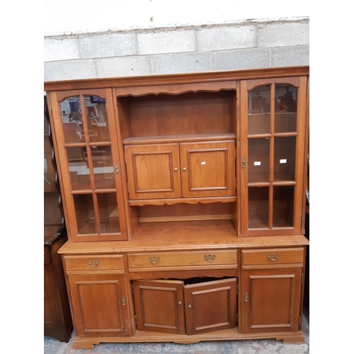 564 - A YOUNGER OAK WALL UNIT WITH FOUR LOWER DOORS, THREE DRAWERS AND TWO UPPER GLAZED DOORS...