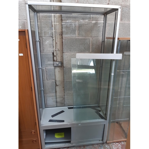 568 - A MODERN METAL AND GLASS SHOP DISPLAY CABINET WITH TWO SLIDING LOWER DOORS AND TWO SLIDING UPPER DOO...