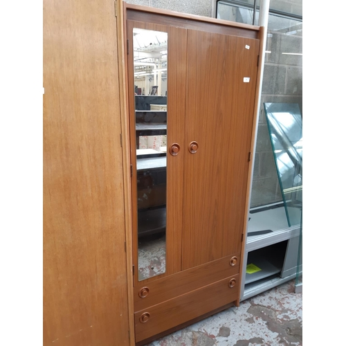 569 - A RETRO TEAK EFFECT SINGLE WARDROBE WITH TWO LOWER DRAWERS AND TWO UPPER DOORS...