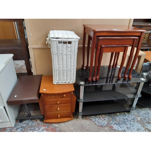 602 - FIVE ITEMS TO INCLUDE A MAHOGANY NEST OF THREE TABLES, BLACK GLASS TV STAND, WHITE WICKER LAUNDRY BA...