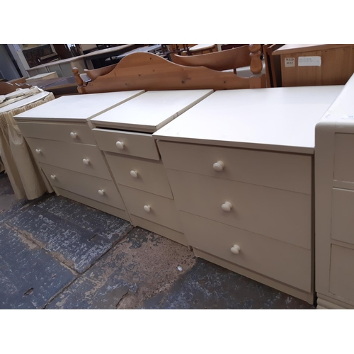 609 - A MODERN WHITE LAMINATE THREE PIECE BEDROOM SUITE COMPRISING CHEST OF THREE DRAWERS, BEDSIDE CHEST O...