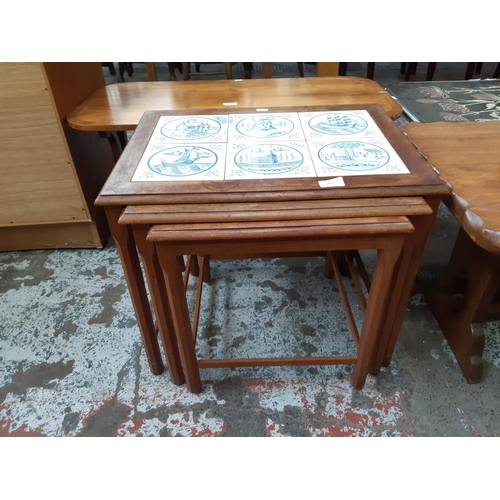 657 - A RETRO TEAK FRAMED NEST OF THREE TABLES EACH HAVING BLUE AND WHITE TILED INSERT...