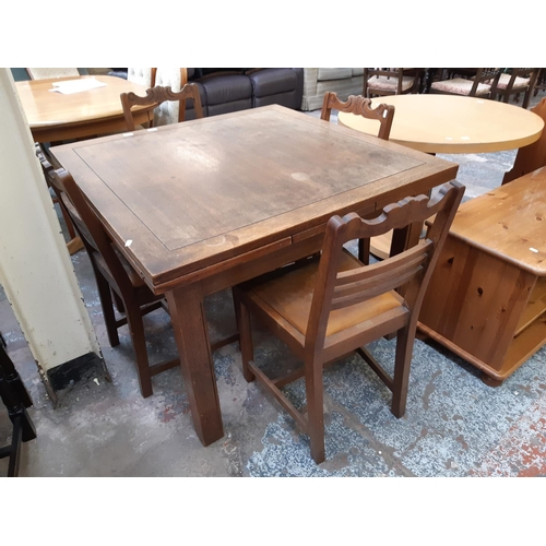 663 - A VINTAGE OAK DRAW LEAF DINING TABLE AND FOUR OAK FRAMED DINING CHAIRS WITH TAN LEATHER UPHOLSTERED ...