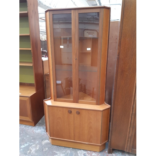 671A - A GOOD QUALITY VINTAGE TURNIDGE TEAK CORNER CABINET WITH TWO LOWER DOORS, TWO GLAZED DOORS AND TWO I...