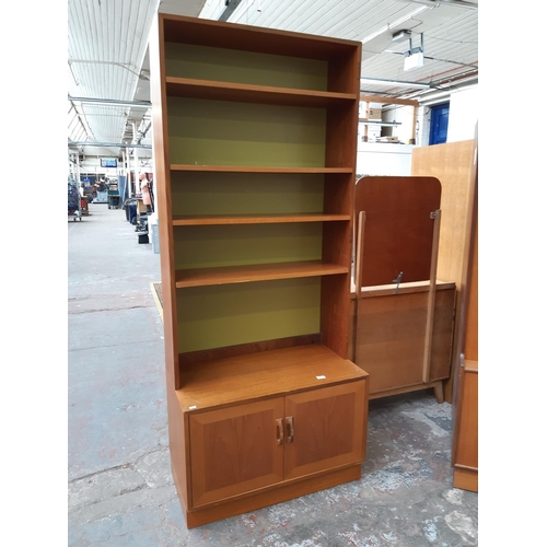 671B - A RETRO G-PLAN RED LABEL TEAK BOOKCASE WITH TWO LOWER CUPBOARD DOORS AND FOUR UPPER SHELVES...