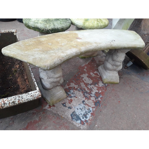 200 - A RECONSTITUTED STONE HALF MOON TWO SEAT GARDEN BENCH WITH SQUIRREL DESIGN SUPPORTS...