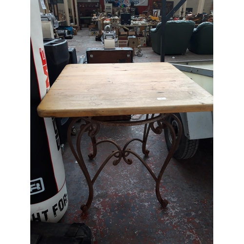 32 - A WOODEN SQUARE TOPPED PATIO TABLE ON ORNATE WROUGHT IRON BASE...