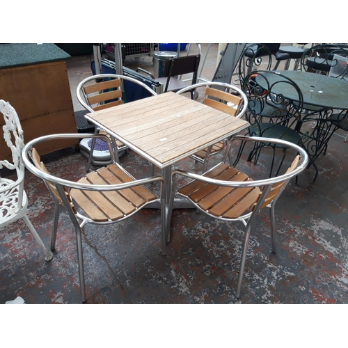 34 - A FIVE PIECE BISTRO STYLE PATIO SET COMPRISING SQUARE TOPPED WOODEN TABLE WITH PEDESTAL BASE AND FOU...