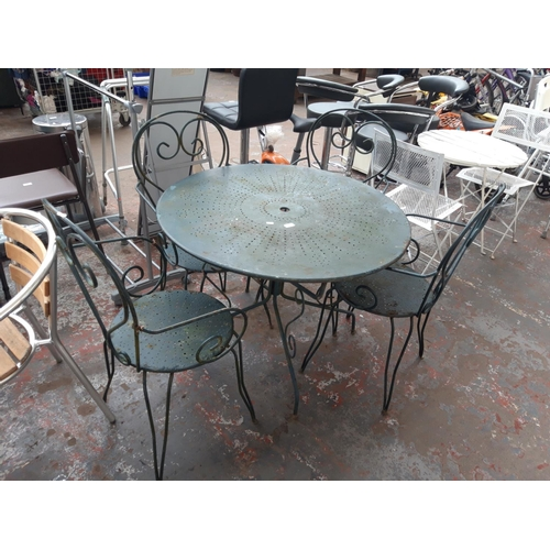 35 - A FIVE PIECE PATIO SET COMPRISING GREEN PAINTED CIRCULAR METAL TABLE AND FOUR MATCHING CHAIRS...