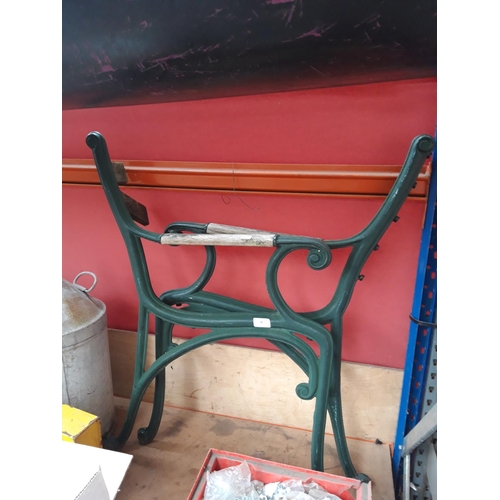 46 - A PAIR OF GREEN PAINTED CAST IRON ORNATE BENCH ENDS WITH WOODEN ARMS...