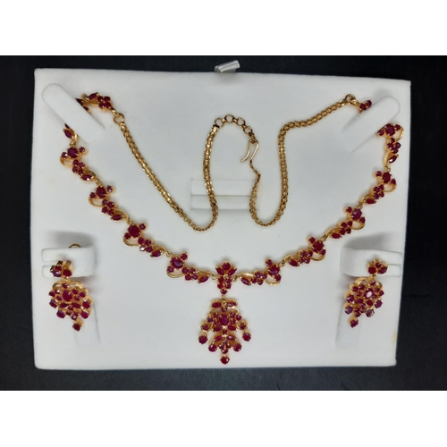 An excellent quality Joyalukkas 22ct Indian yellow gold necklace and earring set, the earrings each having 22 inset rubies, the necklace pendant having 26 inset rubies and the chain having 98 inset rubies - total approx. weight 41 grams