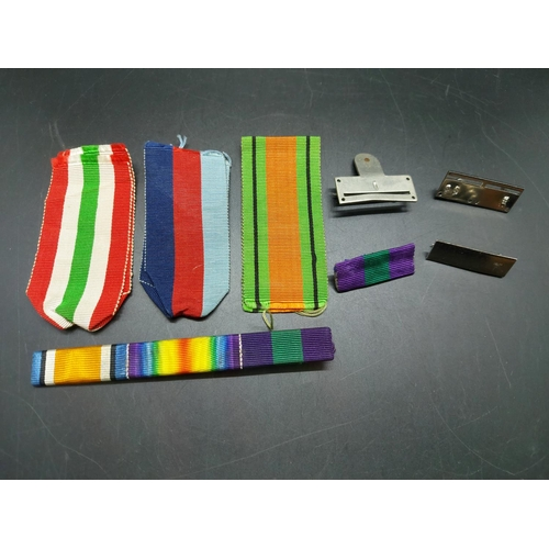 9 - A collection of various militaria to include medal bars, ribbons, three empty medal boxes and two WW...