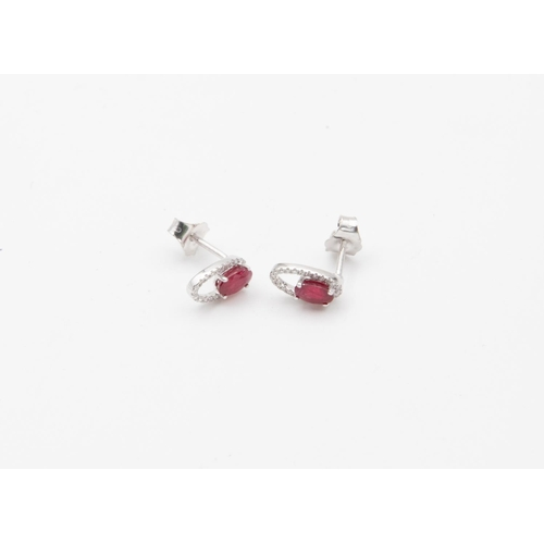 41 - Pair of 18 Carat White Gold Set Ruby and Diamond Halo Stud Earrings Oval Mixed Cut Rubies Claw Set t...