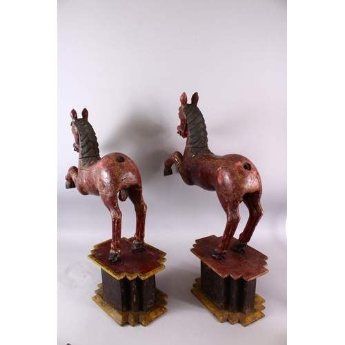 3 - A LARGE PAIR OF CHINESE TANG STYLE CARVED WOODEN HORSE FIGURES, both slotted upon separate pedestal ...