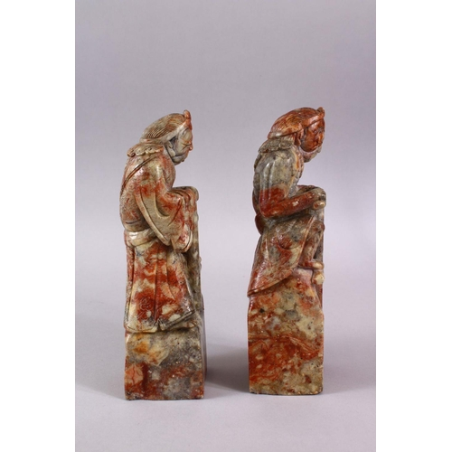 33 - A PAIR OF CHINESE CARVED SOAPSTONE FIGURES OF DEMONS, each demon depicted upon a rocky outcrop with ...