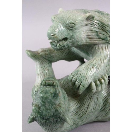 37 - A CHINESE CARVED GREEN HARD STONE MODEL OF TWO PLAYING BEARS, 14cm high x 18cm wide.