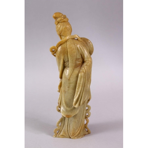 38 - A CHINESE CARVED SOAPSTONE FIGURE OF GUANYIN, stood holding a fan 24cm high.