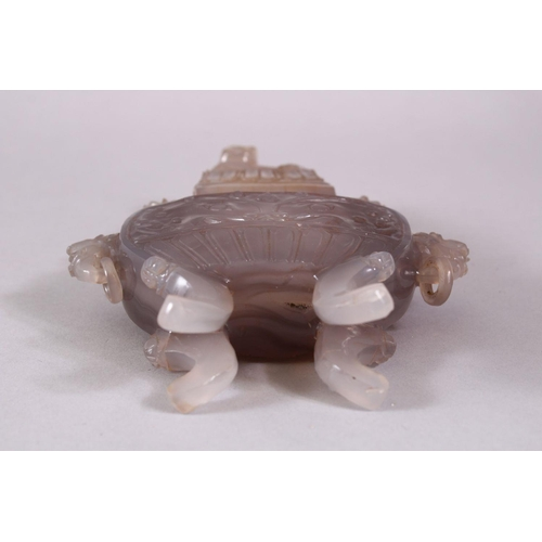 41 - A CHINESE CARVED AGATE VASE AND COVER, with four carved lion dog head handles and rings, stood upon ...