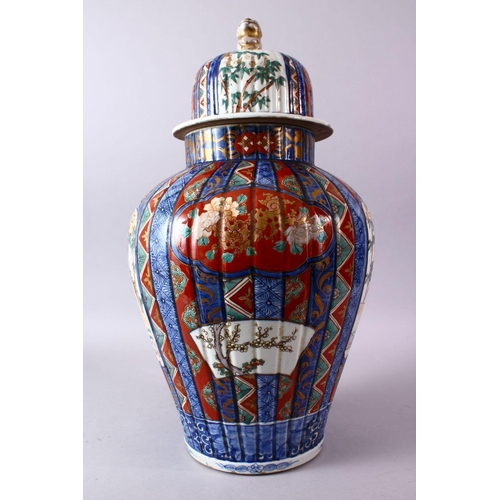 52 - A LARGE IMARI VASE AND COVER, the ribbed body painted with panels of flowers and figures, the cover ...