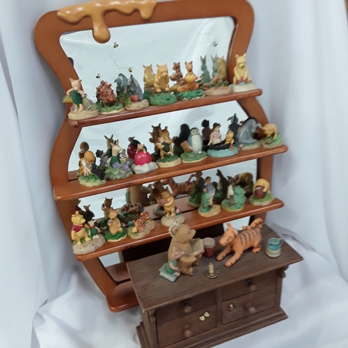 1046 - A wall hanging mirrored back Winnie the Pooh shelf with a quantity of Lenox Thimble collection ornam...