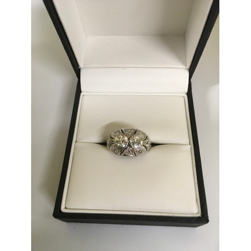 336 - An Art Deco style diamond ring with two central collet set diamonds surrounded by eight small diamon...