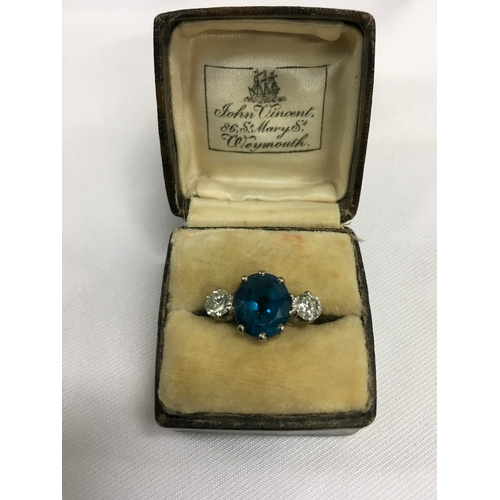 345 - A three stone ring set with large central Topaz flanked by two smaller diamonds set in platinum with...