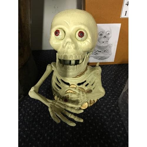 1042 - A skeleton money box.(194)...