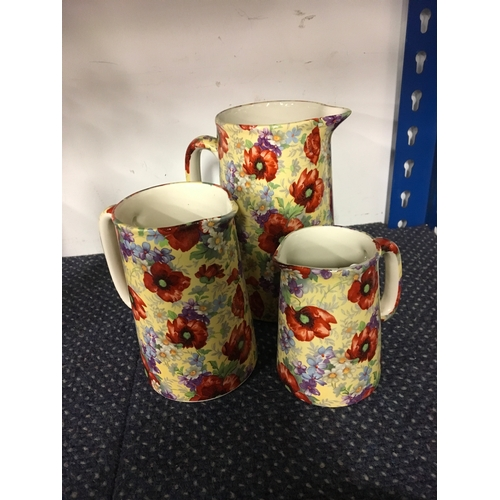 1047 - Three graduated floral Ballyporeen (Irish) jugs....