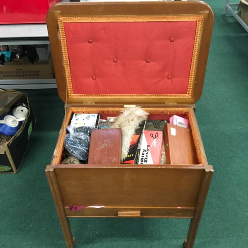 1127 - A sewing box on casters containing associated sewing items....