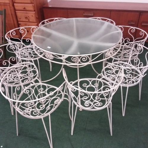 1496 - A wrought iron glass topped circular garden table with eight chairs....