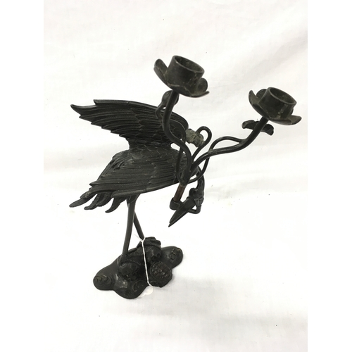 21 - A black candlestick in the shape of a crane....