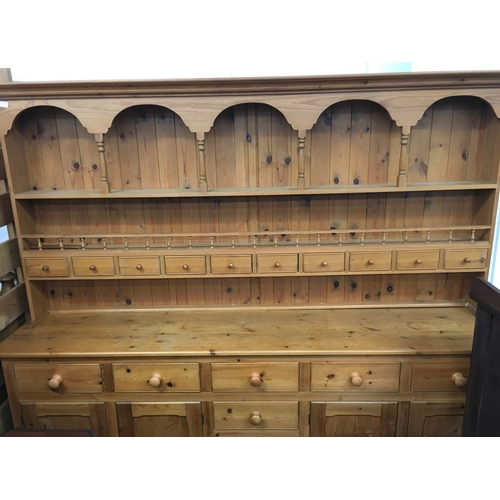 1608A - A pine dresser with an arched plate rack, ten spice drawers and gallery rail. 218cm in length....