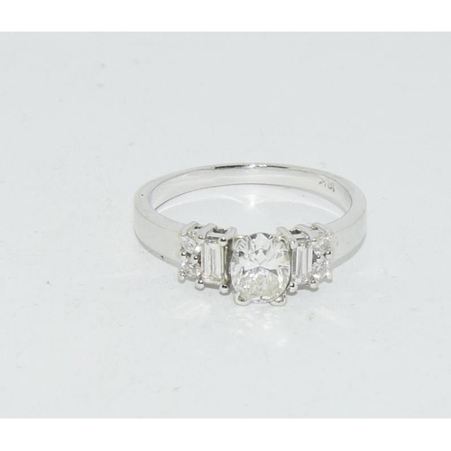 11 - A 1 Carat plus Diamond cushion cut solitaire with baguettes sides, ring in 18ct White gold. Size Q....
