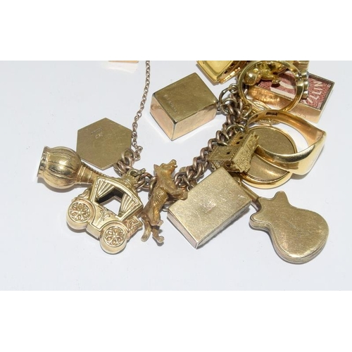 128 - A 9ct gold ladies charm bracelet to included 40 gold charms including diamond ring, sovereign coin a...