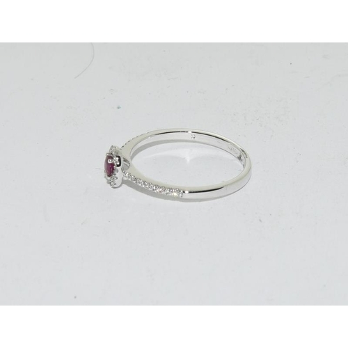 502 - An 18ct white gold ruby and diamond set ring. Size M....