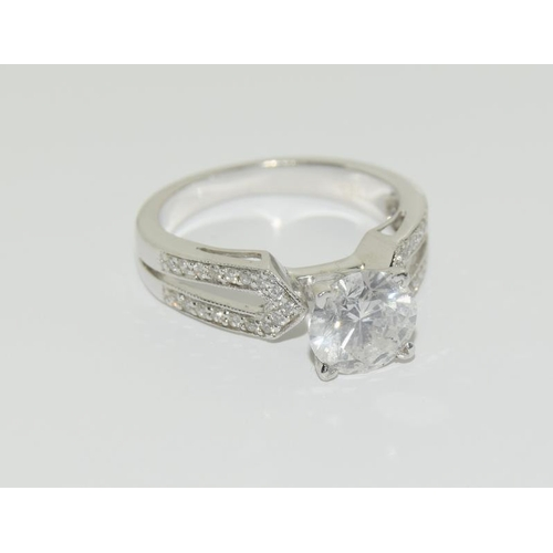 373 - A 14 carat white gold diamond ring, the central stone of 1.6 carats flanked by a double row of diamo...
