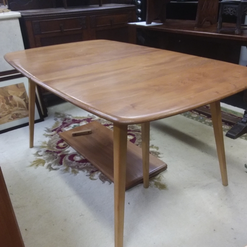 485 - An Ercol light wood dining table with two spare leaves....